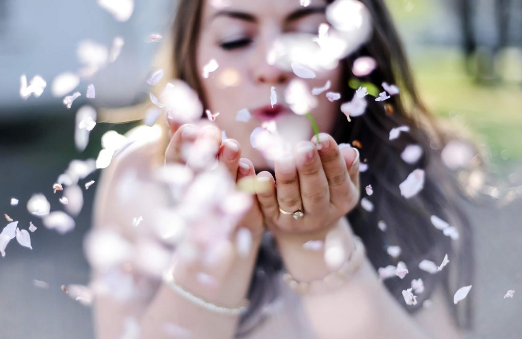 Girl blowing flower petals
