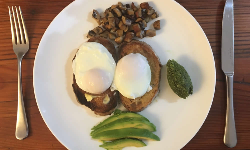 Eggs on toast with avocado and pesto